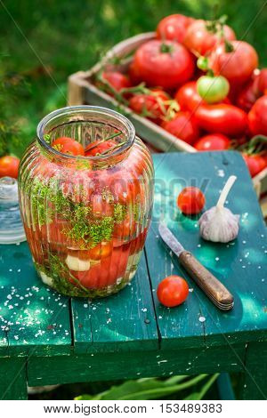 During pickling tomatoes with homemade ingredients on old wooden table