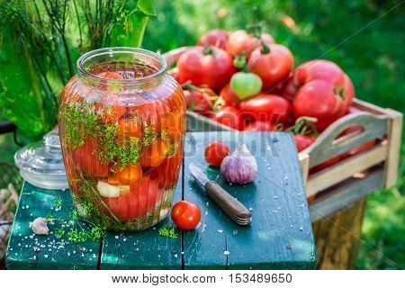 Pickled tomatoes in the garden on old wooden table
