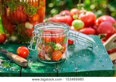 Closeup of pickled tomatoes in summer on old wooden table