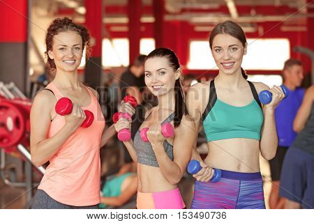 Portrait of young sportive women with dumbbells in gym