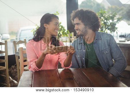 Couple looking at each other while holding mobile phone in cafeteria