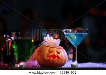 Cocktail and Halloween decor prepared for party, on blurred background