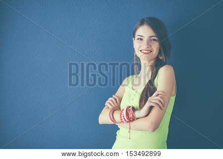 Young woman standing near dark wall with crossed hand .
