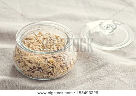 Dry rolled oatmeal in jar on tablecloth.