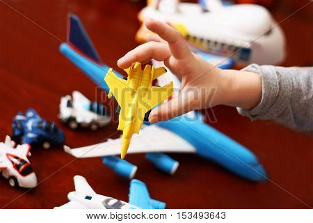 Part of the image of a child playing with a collection of toy plastic airplanes.