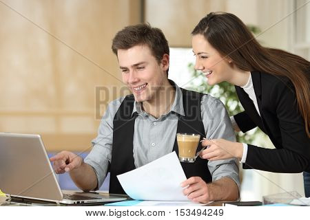 Two partners coworking watching content online in a computer on a desktop at office