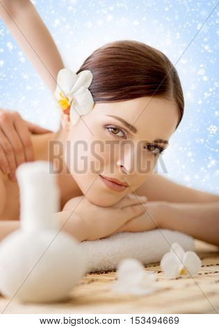 Beautiful, young and healthy woman in winter spa salon. Massage treatment over Christmas background with snow. Traditional medicine and healing concept.