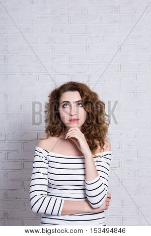 Idea Concept - Young Woman Dreaming About Something Over White Brick Wall