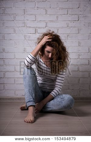 Unhappy Woman With Depression Or Headcahe Sitting On The Floor Over Brick Wall