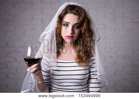 Portrait Of Sad Bride Crying And Drinking Wine