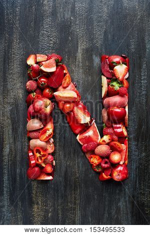 Flat lay series of organic red produce fruit and vegetables shaped into letters of alphabet, design element poster spelling layout