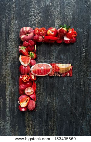 Complete flat lay collection of alphabet letters made from red fruit and vegetables on dark distressed background, overhead set