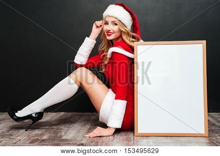 Happy lovely young woman in santa claus costume sitting near blank white board over black background