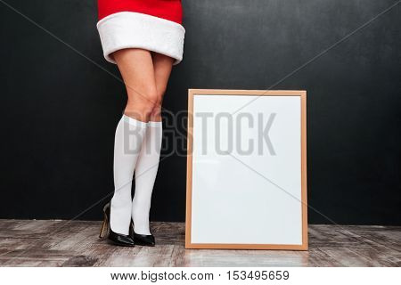 Beautiful legs of young woman in santa claus costume standing near blank white board over black background
