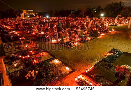 Ljubljana Slovenia - November 1 2013: candles and lantern burning on graves at Cemetery at night for a catholic - christian holiday All Saints' Day. Solemnity of All Saints. All Hallows eve. November 1st. Feast of All Saints. Hallowmas. All Souls' Day.