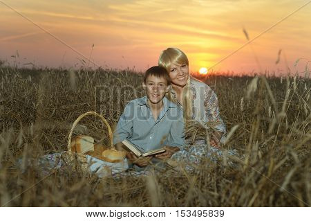 Mom with son with her  on wheat field at a picnic on sunset