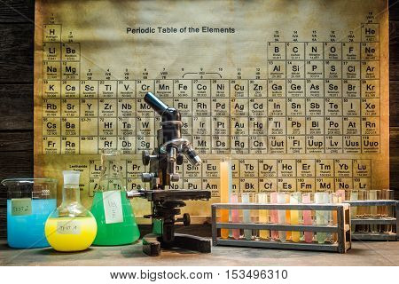 Chemical laboratory with microscope and sample on old wooden table