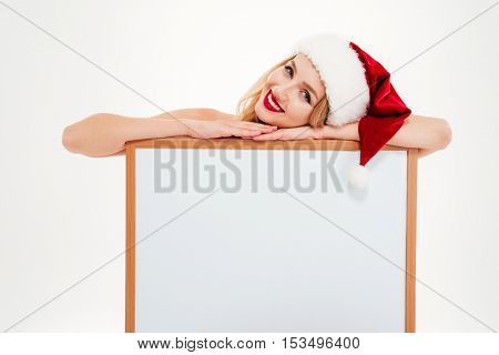 Smiling beautiful young woman in santa claus costume with blank screen board over white background