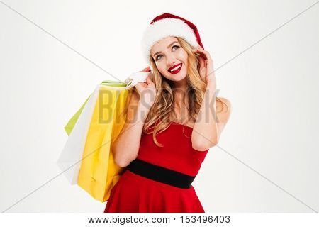 Smiling lovely young woman in santa claus costume with shopping bags over white background