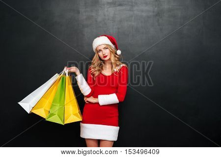 Thoughtful young woman in santa claus costume holding shopping bags and thinking over black background