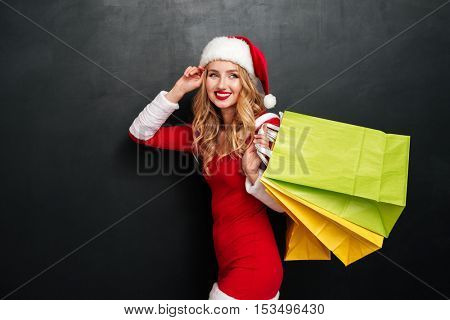 Cheerful beautiful young woman in santa claus costume walking and holding shopping bags over black background
