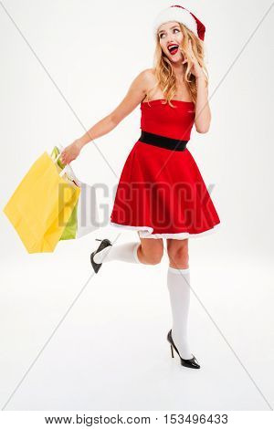 Happy beautiful young woman in santa claus costume running and holding shopping bags over white background