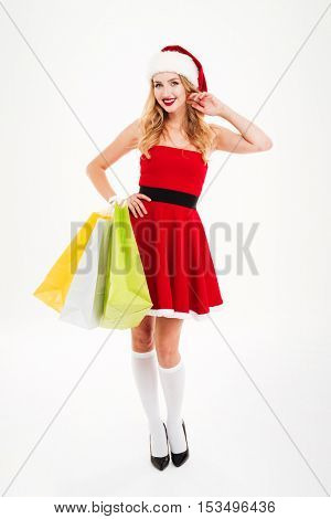 Full length of cheerful charming young woman in santa claus costume standing and holding shopping bags over white background
