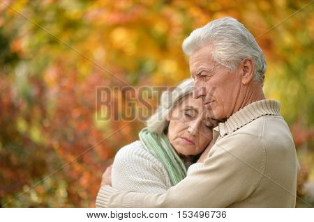 Portrait of a sad elderly couple standing embracing outdoors