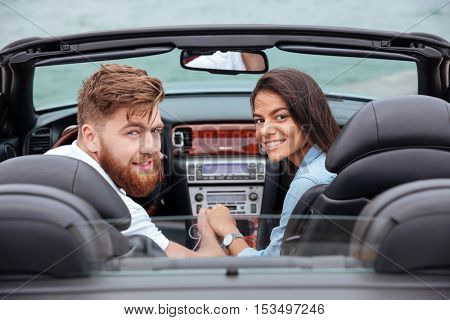 Couple looking back and smiling in white cabriolet outdoors
