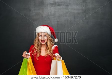 Happy lovely young woman in santa claus costume with shopping bags over black background