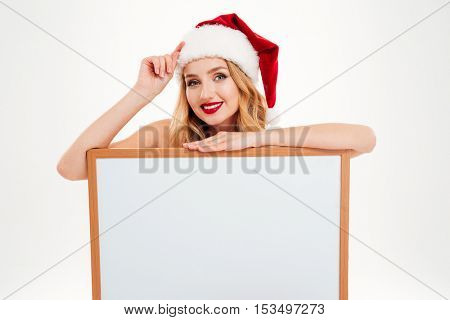 Cheerful cute young woman in santa claus costume holding blank screen board over white background