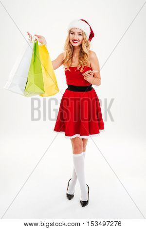 Smiling cute young woman in santa claus costume with cell phone and shopping bags over white background