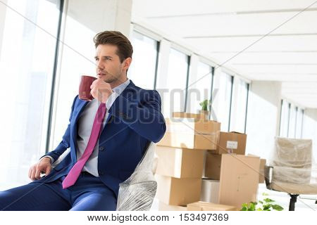 Portrait of young businessman drinking coffee with moving boxes in background at office