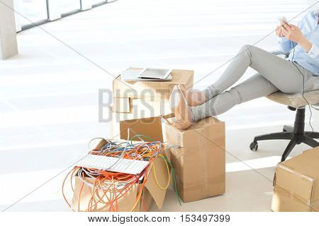 Low section of businesswoman holding mobile phone with feet up on cardboard box at office