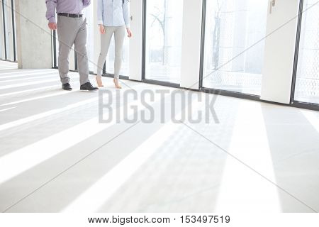 Low section of business people walking by windows in empty office