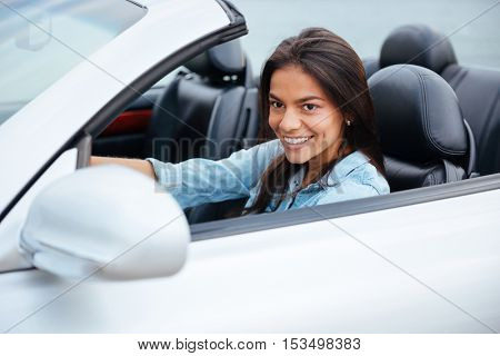 Portrait of young brunette girl driving cabriolet