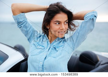 Close up portrait of a young brunette woman standing next to her new car at the seaside