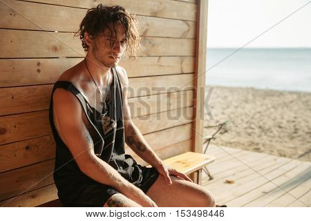 Stylish young serious man sitting at the beach shack