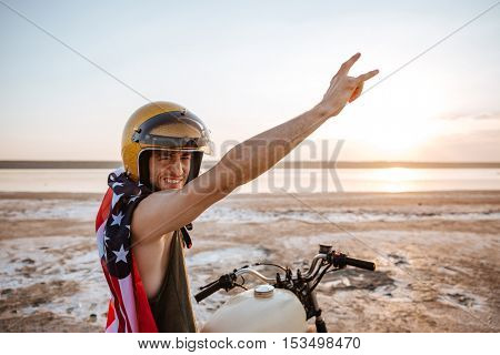 Smiling brutal man in golden helmet and american flag cape sitting on his motocycle with hands up in the air