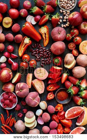 Fresh food raw produce in red colors, cut sliced cross section flatlay overhead filled frame food layout