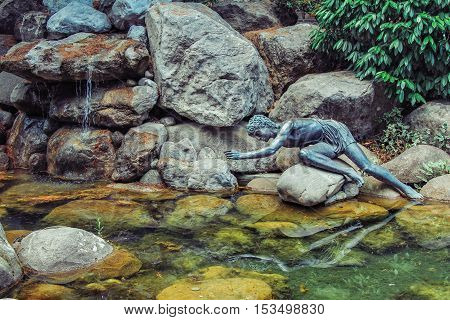 Partenit Village, Crimea/Ukraine - June 07, 2012: Copper sculpture of Narcissus sitting on a rock in a pond, admiring self reflection on a water surface, legend scene reconstruction.