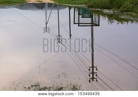 Three concrete electric pole reflected in a big puddle