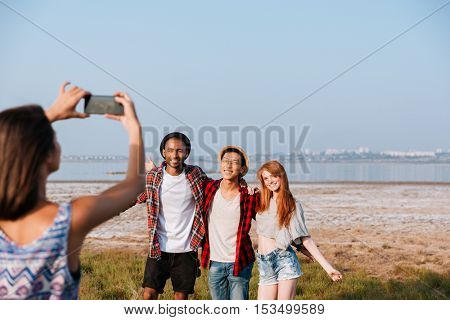 Woman standing and taking pictures of her friends with mobile phone outdoors