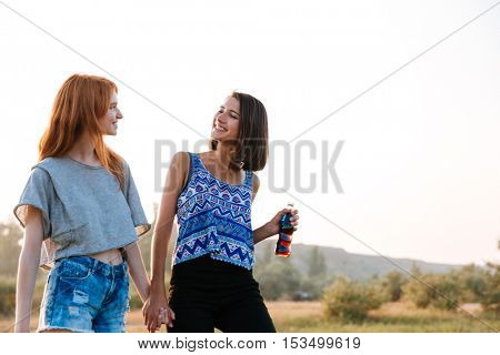Two happy young women walking and drinking soda outdoors