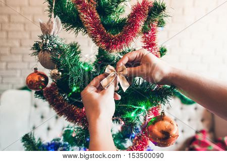 Christmas tree decorating close-up. Hand hanging golden bow on beautiful festive pine tree. Holiday, happy family, party concept