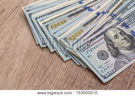 100 american dollar bills on wooden desk