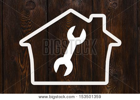 Paper house with wrench, spanner inside. Housing, repair concept. Dark wooden background. Abstract conceptual image
