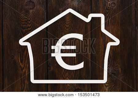 Paper house with euro sign inside. Housing, money concept. Dark wooden background. Abstract conceptual image
