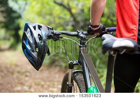 Male cyclist walking with mountain bike in countryside