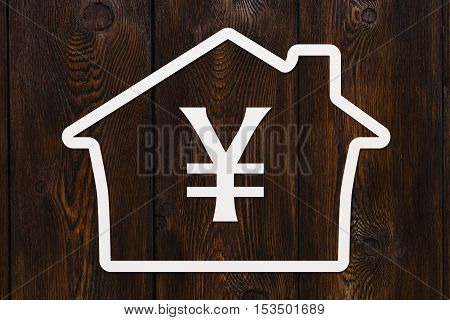 Paper house with yen sign inside. Housing, money concept. Dark wooden background. Abstract conceptual image